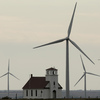 Wind turbines dwarf a church near Wilson, Kan. Although Congress voted to extend a wind energy tax credit, the temporary uncertainty dealt a blow to the industry.