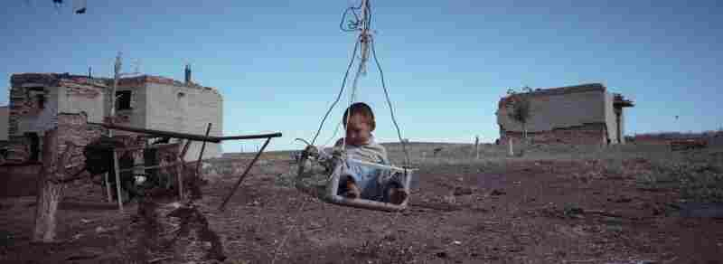 Erasu Sokolov sits in a swing by the former military barracks, which his family uses as a house, August 2011.