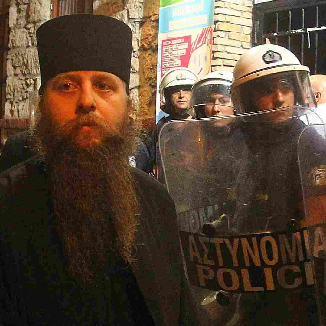 A Greek Orthodox priest is blocked by riot police as he takes part in a protest outside an Athens theater in October. The play, Corpus Christi, portrays Jesus and his apostles as gay men living in modern-day Texas. The director and the cast have been charged under Greece's blasphemy laws.