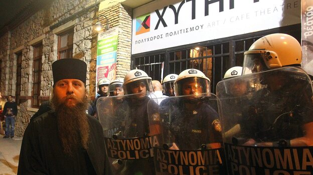 A Greek Orthodox priest is blocked by riot police as he takes part in a protest outside an Athens theater in October. The play, Corpus Christi, portrays Jesus and his apostles as gay men living in modern-day Texas. The director and the cast have been charged under Greece's blasphemy laws. (EPA/Landov)
