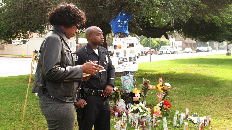 Officers Carol Mitchell and John Hill investigate the death of a disabled teen who was struck and killed by a hit-and-run driver in Los Angeles. (Gloria Hillard for NPR)