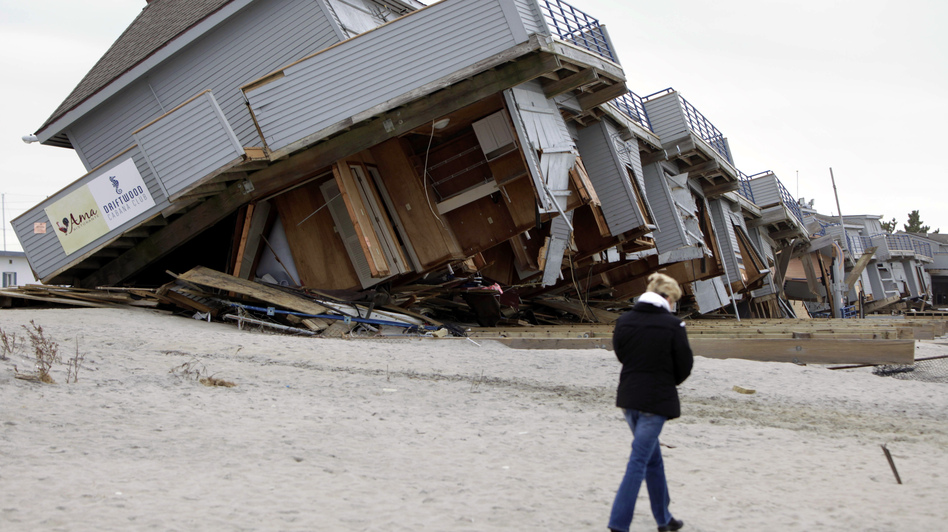 A woman walks past a cabana complex pulled off its foundations by Superstorm Sandy in Sea Bright, N.J., in November. (AP)