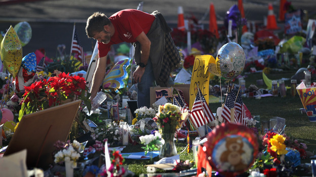John Underhill waters flowers at a makeshift memorial for shooting victims outside the University Medical Center in Tucson, Ariz., on Jan. 20, 2011. Many of the plants and flowers at area memorials were replanted at a community garden. (Getty Images)