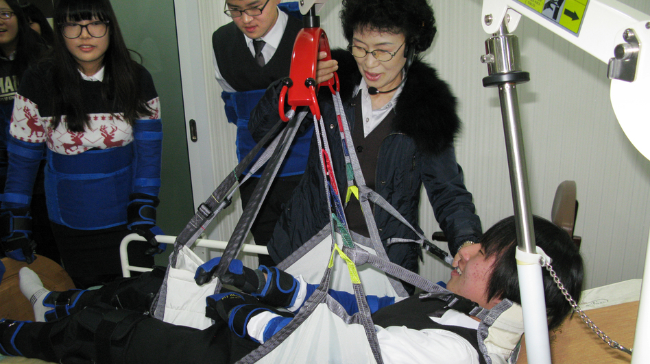 High school student Kim Dong-hyun undergoes a simulated experience as an incapacitated elderly person who is hoisted from his bed into a chair by means of a winch and sling. Training at the Seongnam Senior Complex outside Seoul is intended to help young people understand what the elderly are experiencing. (NPR)