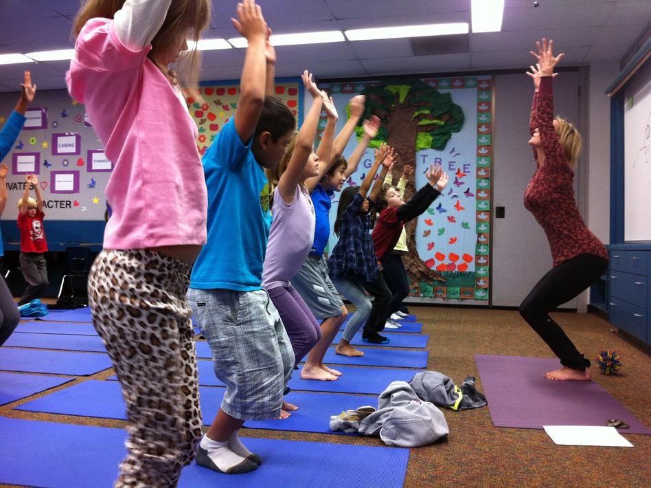 Third-graders at Olivenhain Pioneer Elementary School in Encinitas, Calif., perform chair pose with instructor Kristen McCloskey last month. (Kyla Calvert for NPR)