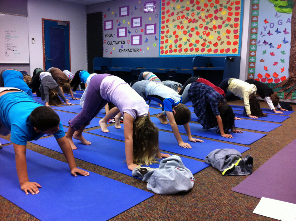 The third-graders at Olivenhain Pioneer take three deep breaths in the downward dog position during one of their two weekly yoga classes. (Kyla Calvert for NPR)