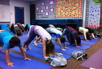 The third-graders at Olivenhain Pioneer take three deep breaths in the downward dog position during one of their two weekly yoga classes.