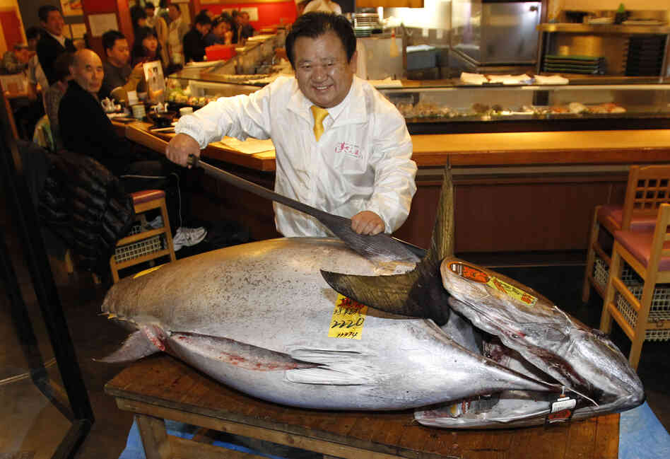 Sushi chain owner Kiyoshi Kimura poses with a bluefin tuna in front of his Sushi Zanmai restaurant in To