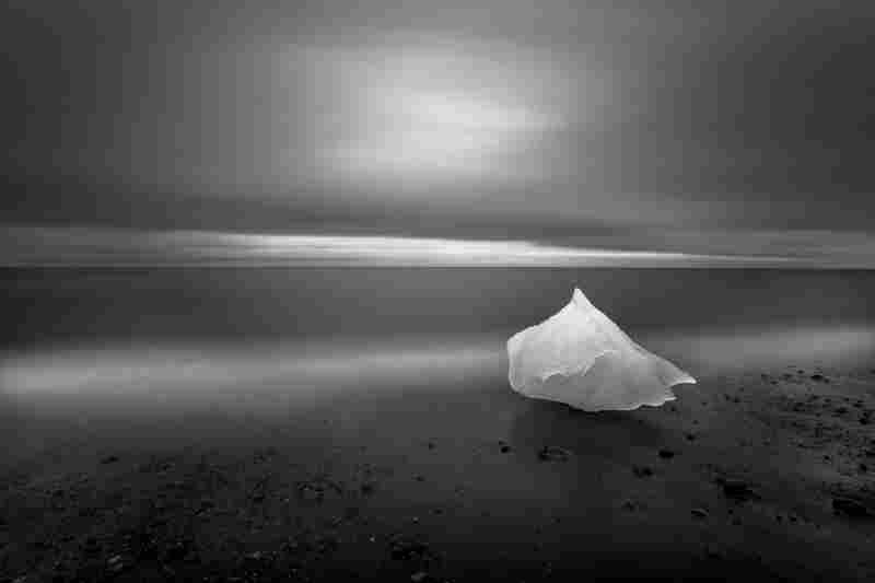 """""""Glacial ice washes ashore after calving off [a] glacier on Iceland's eastern coast. During the waning light of summer this image was created over the course of a 4-minute exposure while the photographer backlit the grounded glacial ice with a headlamp for 2 of those 4 minutes."""""""