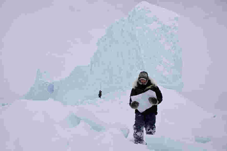 """Chipping ice off an iceberg is a common way for the Inuit community to retrieve fresh drinking water while on the land. During a weekend-long hunting trip, we came upon this majestic iceberg frozen in place. It was a perfect opportunity to grab enough ice and drinking water for the remainder of the trip.'"