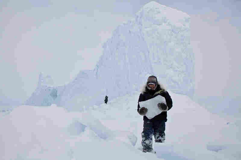"""""""Chipping ice off an iceberg is a common way for the Inuit community to retrieve fresh drinking water while on the land. During a weekend-long hunting trip, we came upon this majestic iceberg frozen in place. It was a perfect opportunity to grab enough ice and drinking water for the remainder of the trip.'"""