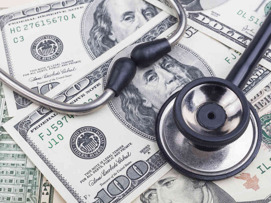Black stethoscope close-up on top of dollar banknotes