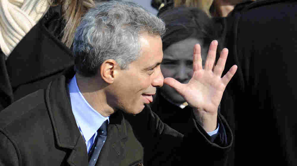Incoming White House Chief of Staff Rahm Emanuel makes a face before President Barack Obama's inauguration in 2009. The person behind him does not look amused.