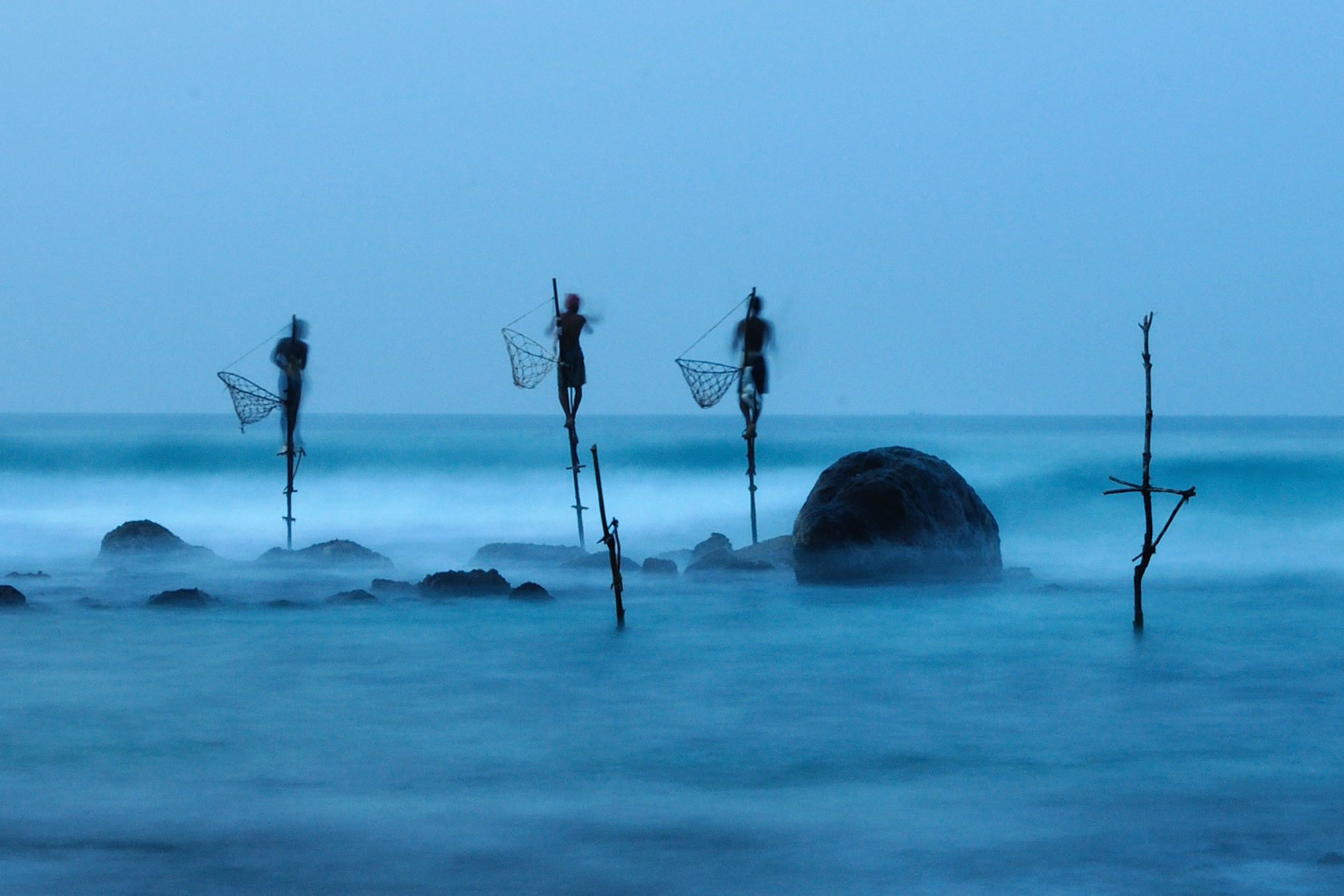 """Stilt fishing is a typical fishing technique only seen in Sri Lanka. The fishermen sit on a cross bar called a petta tied to a vertical pole planted into the coral reef."""
