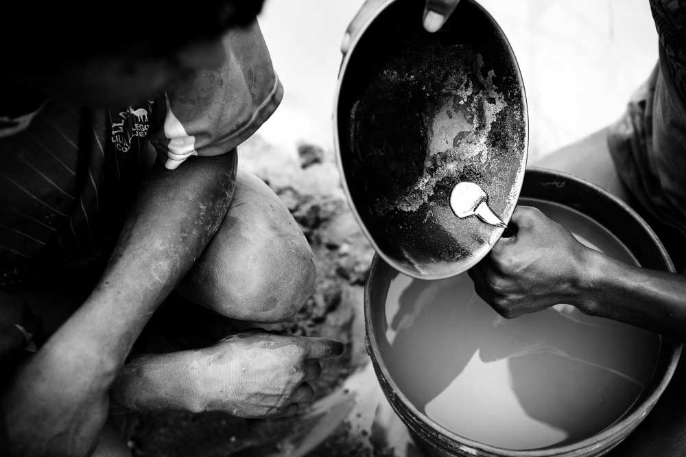 After 12 hours of dredging and another hour separating the gold particles from the sediment, a young miner pours the gold amalgam -- a mix of liquid mercury and gold particles -- into a container, which will then be taken to a gold shop where the mercury is burned off, leaving raw gold.