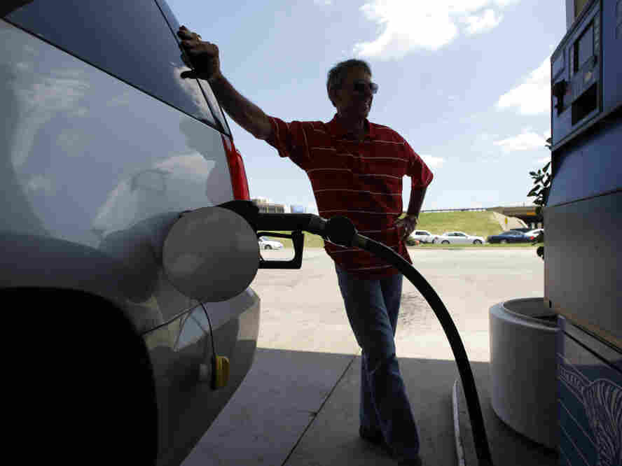 Larry Barnard fills his car with gasoline at an Exxon station in Farmers Branch, Texas, on June 30.