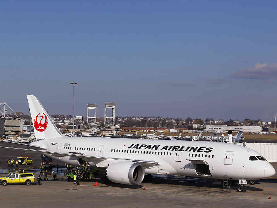 A Japan Airlines Boeing 787 Dreamliner jet aircraft is surrounded by emergency vehicles while parked at a Terminal E gate at Logan International Airport in Boston on Monday. A small electrical fire filled the ca