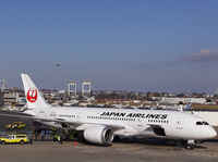 A Japan Airlines Boeing 787 Dreamliner jet aircraft is surrounded by emergency vehicles while parked at a Terminal E gate at Logan International Airport in Boston on Monday. A small electrical fire filled the cabin of the JAL aircraft with smoke about 15 minutes after it landed in Boston.