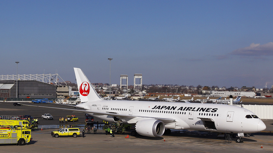 A Japan Airlines Boeing 787 Dreamliner jet aircraft is surrounded by emergency vehicles while parked at a Terminal E gate at Logan International Airport in Boston on Monday. A small electrical fire filled the cabin of the JAL aircraft with smoke about 15 minutes after it landed in Boston. (AP)