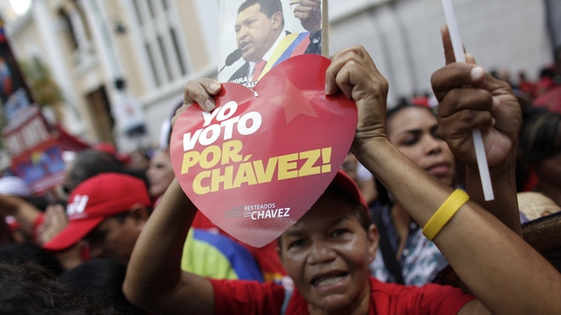 """A supporter of Venezuela's President Hugo Chavez holds a heart-shaped sign that reads in Spanish """"I vote for Chavez!"""" and a picture of Chavez outside the National Assembly in Caracas over the weekend. On Thursday, Chavez is scheduled to be sworn in for a fourth term. Government officials are suggesting the ceremony could be delayed as the president recovers from cancer surgery in Cuba. (AP)"""