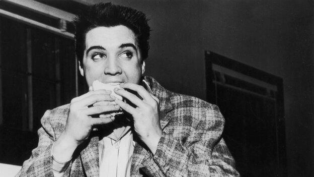 A still-trim Elvis Presley enjoys a sandwich in 1958. His love of fatty foods hadn't caught u