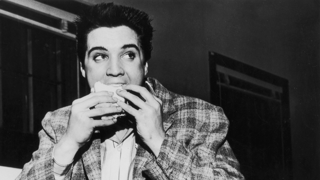 A still-trim Elvis Presley enjoys a sandwich in 1958. His love of fatty foods hadn't caught up to him yet.