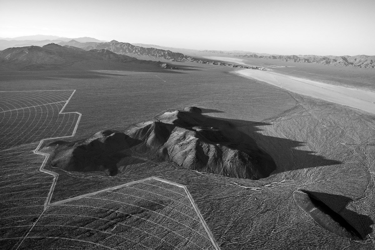 The boundaries of Solar Fields Two and Three move around existing geological formations protruding above the alluvial slope of Ivanpah Basin. Interstate 15 crosses the distant dry lake bed, and Primm, Nev., is seen in the distance. June 2012.