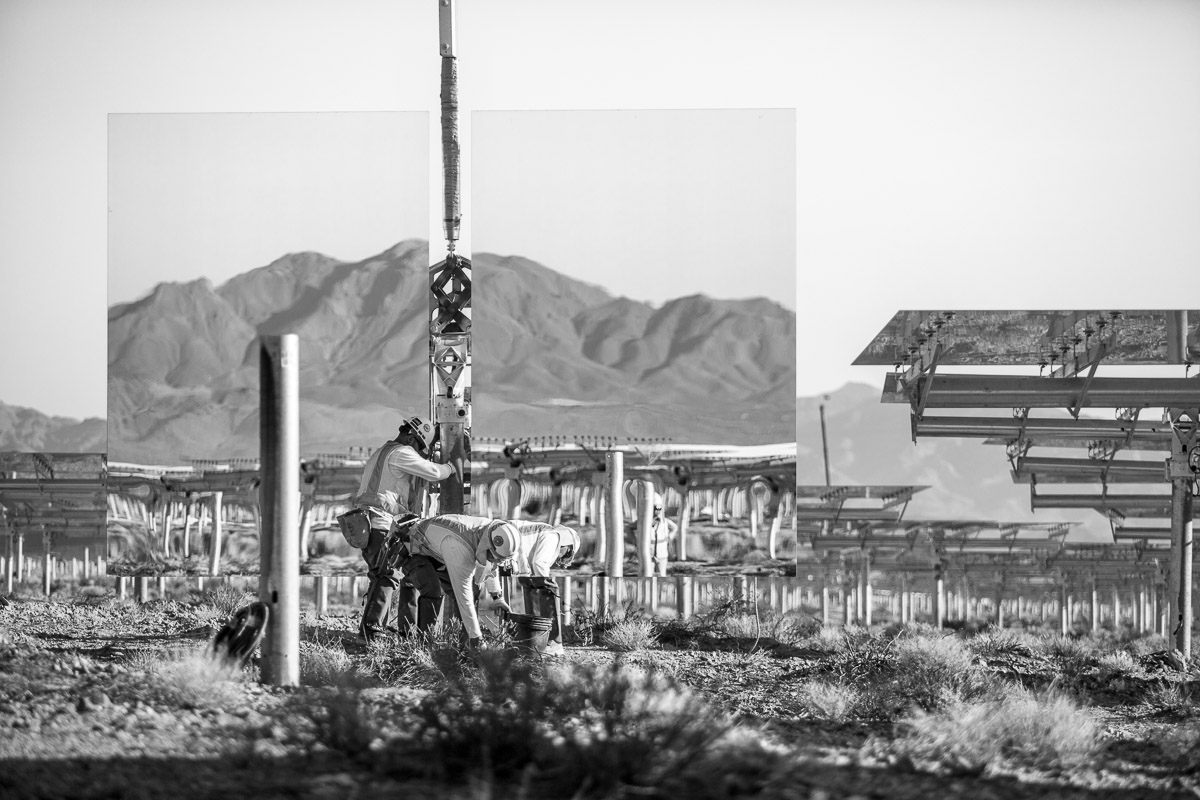 "Workers install a ""heliostat"" -- or a device with a mirror that reflects the sun, or in this case the nearby mountains. Background shows assembled heliostats in ""safe"" or resting position. June 2012."