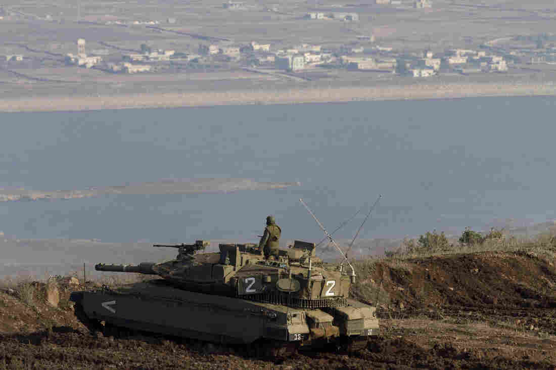 An Israeli tank in the Golan Heights overlooks the Syrian village of Bariqa in November. Israel, which captured the Golan Heights from Syria in 1967, says it's building a fence there because it's concerned about spillover from the Syrian war.
