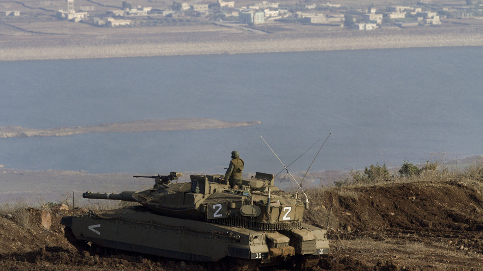 An Israeli tank in the Golan Heights overlooks the Syrian village of Bariqa in November. Israel, which captured the Golan Heights from Syria in 1967, says it's building a fence there because it's concerned about spillover from the Syrian war. (AP)