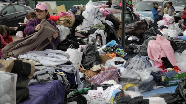 Volunteers sort through piles of donated clothes for Superstorm Sandy victims at an impromptu Staten Island aid station in November. Relief groups are still trying to figure out what to do with donated clothes people sent to New York and New Jersey in Sandy's aftermath. (AP)