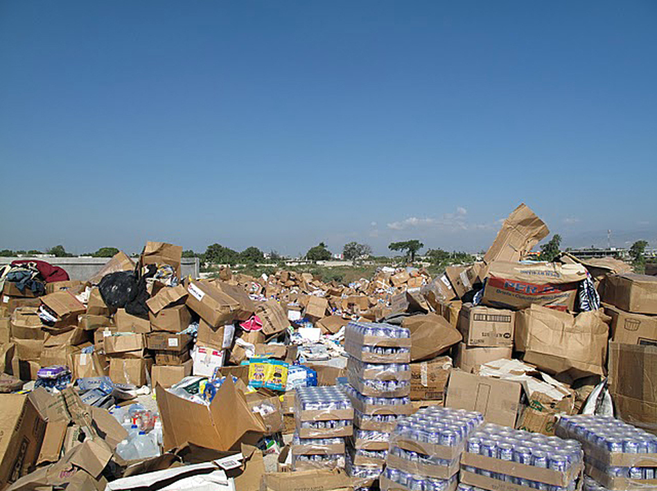 Unsolicited donations of used clothing, bottled water, canned food and personal grooming products piled up following the 2010 earthquake in Haiti. The piles had to be moved aside to make room to stage and deliver critical relief supplies. (Courtesy of the Center for International Disaster Information)
