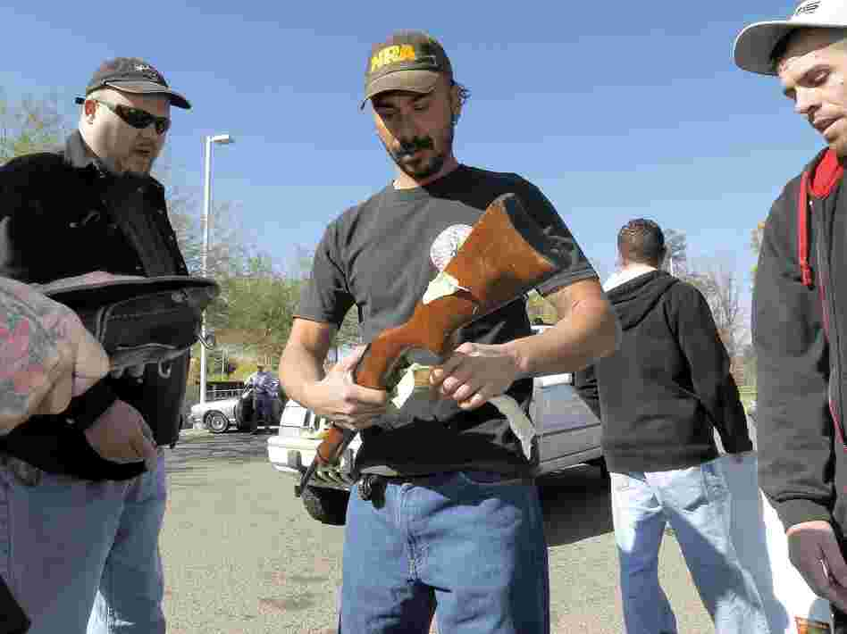 Gun buyers inspect their purchases outside a police station in Tucson, Ariz., on Tuesday. About a dozen buyers offered cash to sellers in the parking lot of a police station where a city councilman had set up a gun buyback program.