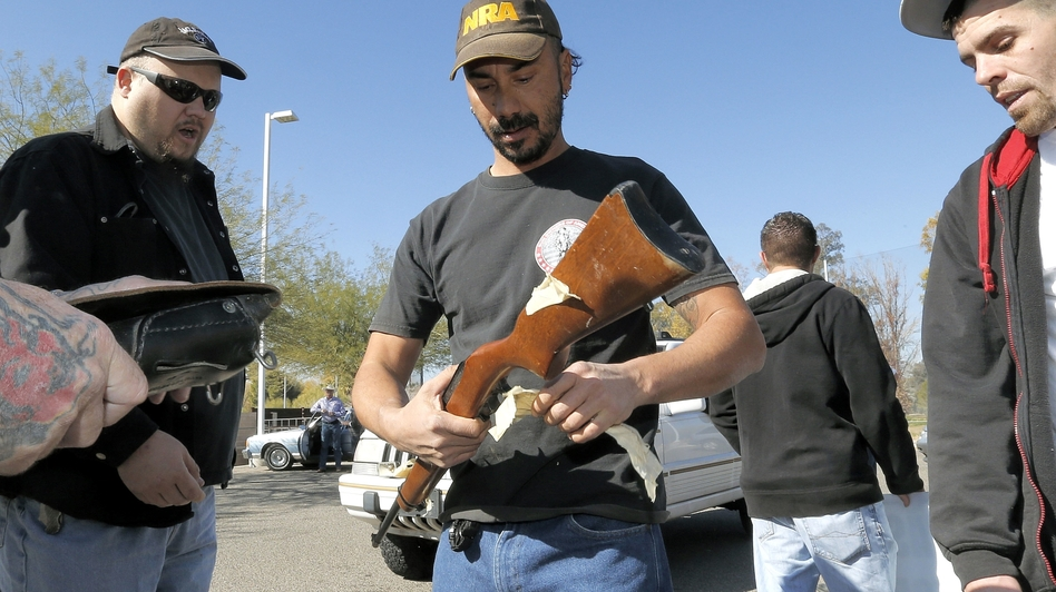 Gun buyers inspect their purchases outside a police station in Tucson, Ariz., on Tuesday. About a dozen buyers offered cash to sellers in the parking lot of a police station where a city councilman had set up a gun buyback program. (AP)