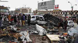 Pakistani police officers and residents gather at the site of a bomb blast that targeted paramilitary soldiers in a commercial area in the city of Quetta, killing 11 people. Later in the day, twin blasts at a snooker club in the city killed at least 80 people.