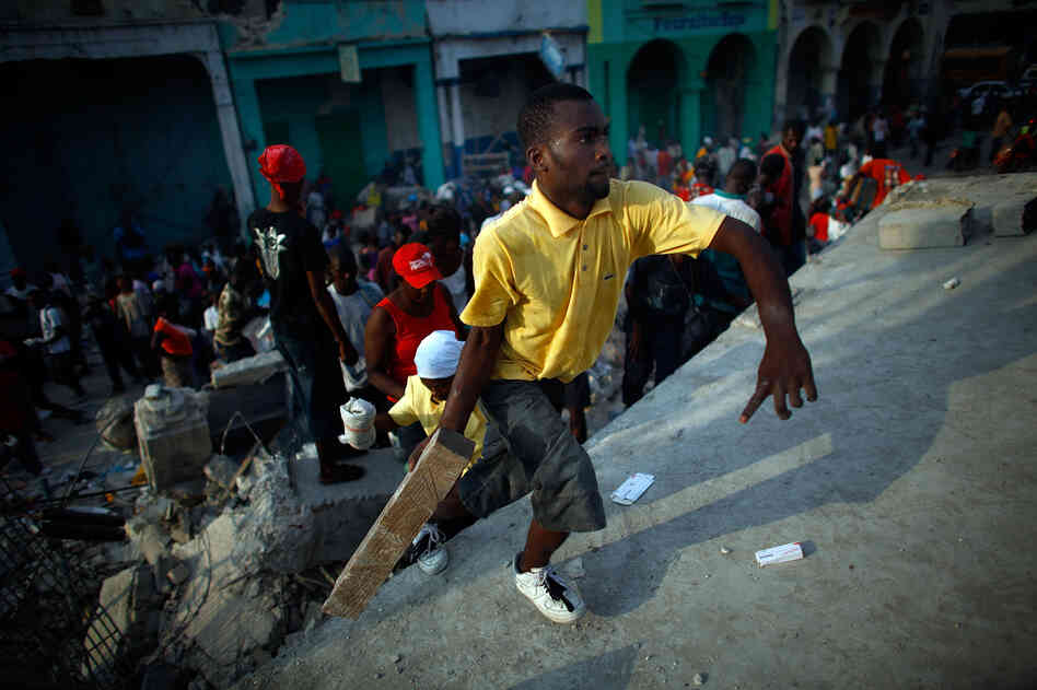 Looters on the roof of a collapsed supermarket in Port-au-Prince, Haiti, Jan. 20, 2010.