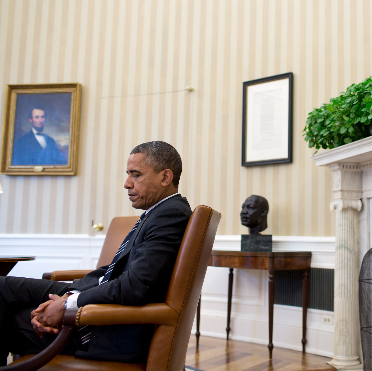 President Obama is seen during a September meeting at the White House, juxtaposed with the paintings of Abraham Lincoln and George Washington, busts of Martin Luther King Jr. and Abraham Lincoln, and the Emancipation Proclamation.
