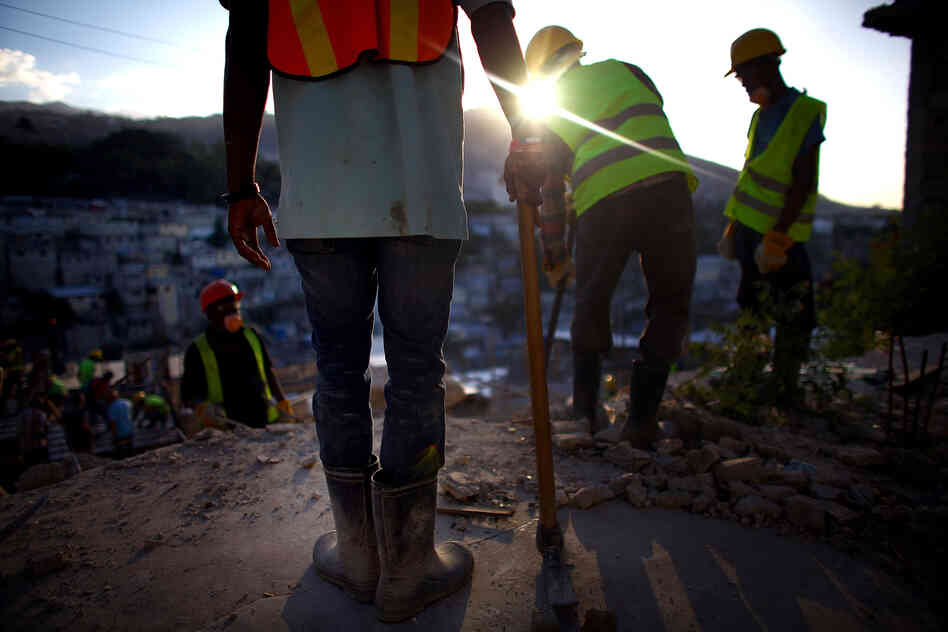 Construction workers overlook the hills above Port-au-Prince near Petionville, where an 18-unit complex is slated to go up this year. Despite billions of dollars in international donations for earthquake relief, only about 5,000 permanent houses have been built.