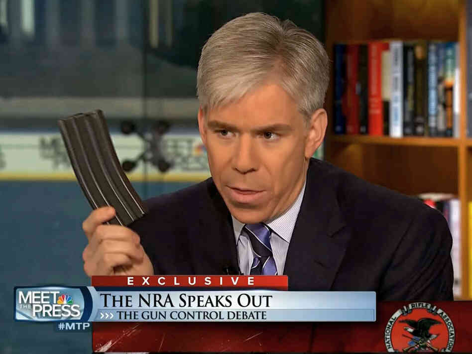 Meet the Press host David Gregory holds what he described as a high-capacity ammunition magazine duri