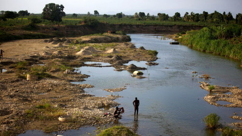 Men bathe in a branch of the Artibonite River outside Saint-Marc. Haiti's cholera outbreak in 2010 began about 60 miles upstream from here. (NPR)