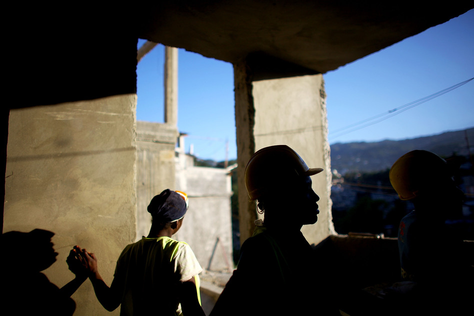 Workers finish the cement walls on a multilevel building in the hills above Port-au-Prince near Petionville. They plan to finish the 18-unit housing facility in 2013. (NPR)