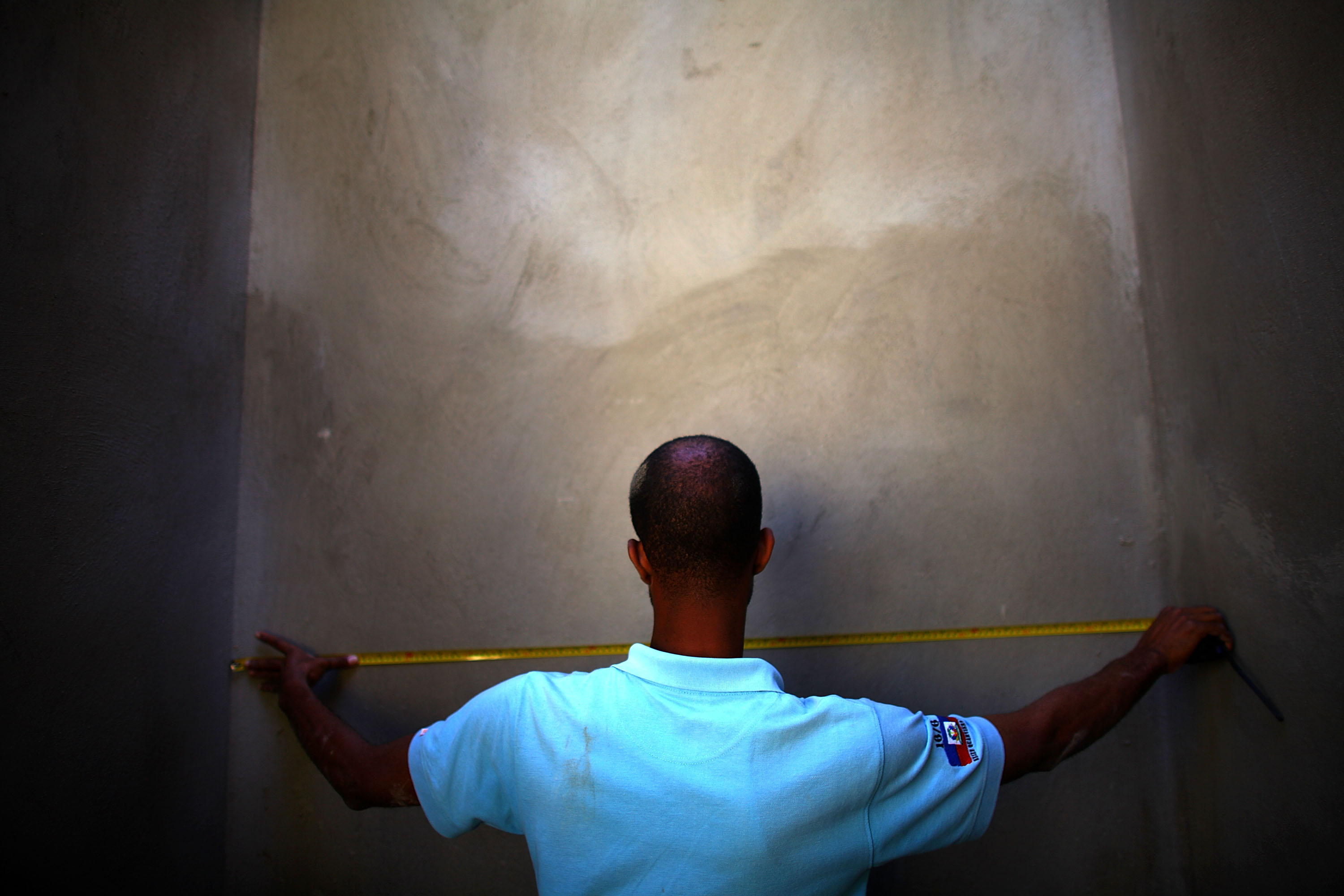A man measures a completed section of a retaining wall at a construction site in the hills above Port-au-Prince near Petionville.