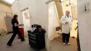 Registered nurse Michelle Newbury and physician assistant Scott Fillman see patients Thursday in a tent set up for people with flu symptoms, just outside the emergency entrance at the Lehigh Valley Hospital in Allentown, Pa