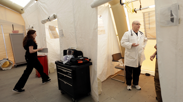 Registered nurse Michelle Newbury and physician assistant Scott Fillman see patients Thursday in a tent set up for people with flu symptoms, just outside the emergency entrance at the Lehigh Valley Hospital in Allentown, Pa. (AP)