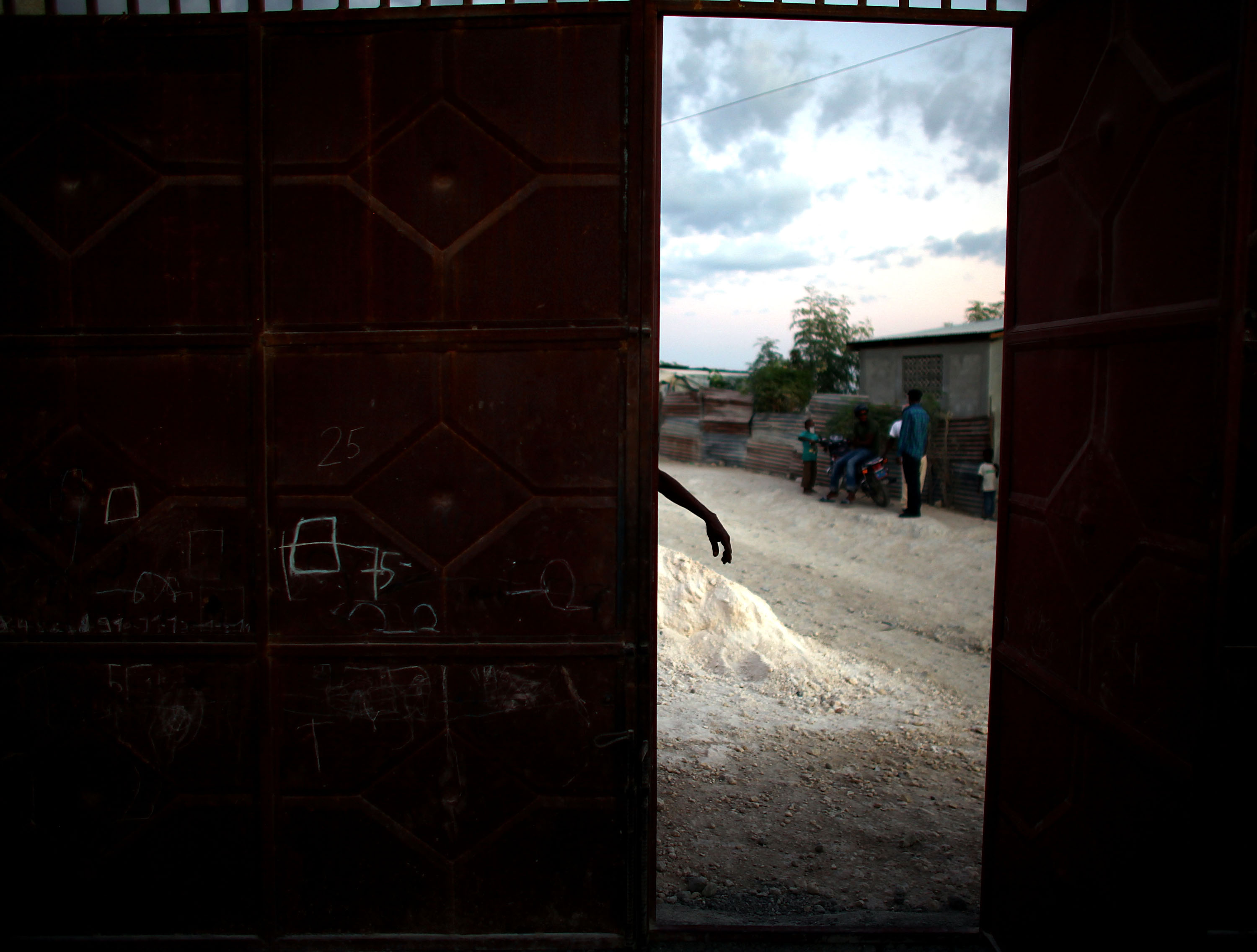 A man works on his steel gate outside of his ramshackle house near Camp Corail, just north of Port-au-Prince.