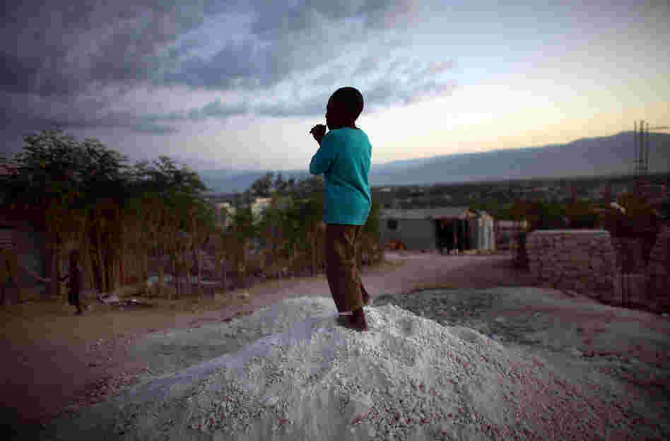 A boy stands on a pile of rocks used for the construction of new homes in the hills overlooking Camp Corail, just north of Port-au-Prince. Squatters are streaming into the area and setting up communities, with little government oversight.