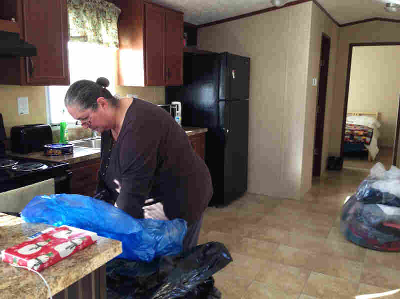 Deborah Rassi, 59, cleans her new kitchen. She's holding a bag of donated clothing, one of many that volunteers left in the new mobile home.