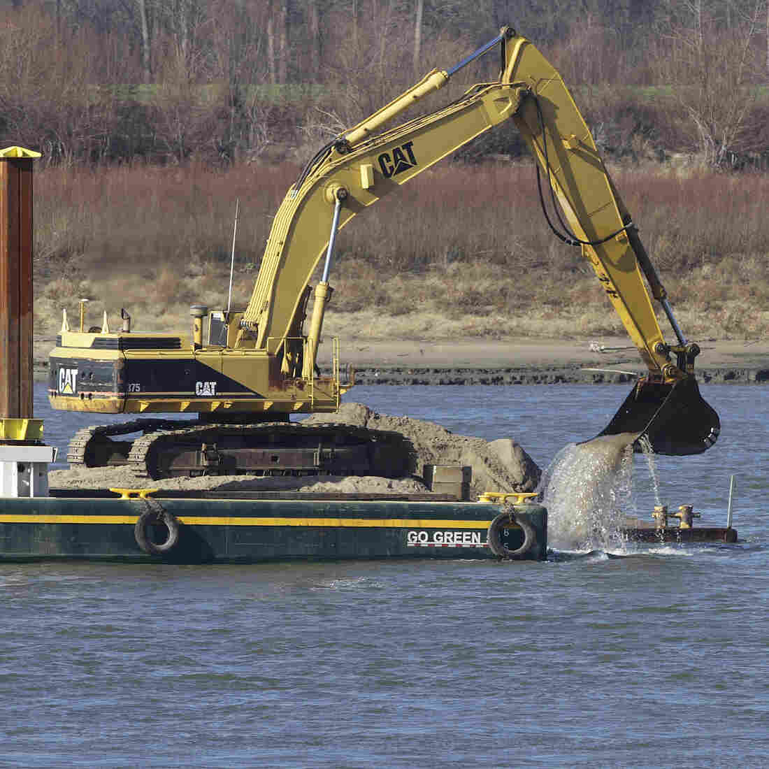 An excavator perched on a barge removes rocks from the Mississippi River in Thebes Ill.