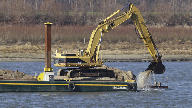 An excavator perched on a barge removes rocks from the Mississippi River in Thebes Ill. (AP)
