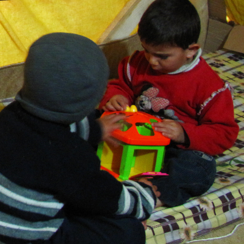 Oula's sons play in her family's tent at the al-Marj refugee camp in Lebanon's Bekaa Valley. A small gas stove in the center of the tent keeps the family warm and boils water for tea.
